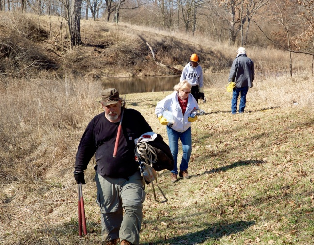 Volunteers carrying loppers, tools on short-grass path, in hilly terrain, covered with native plants.
